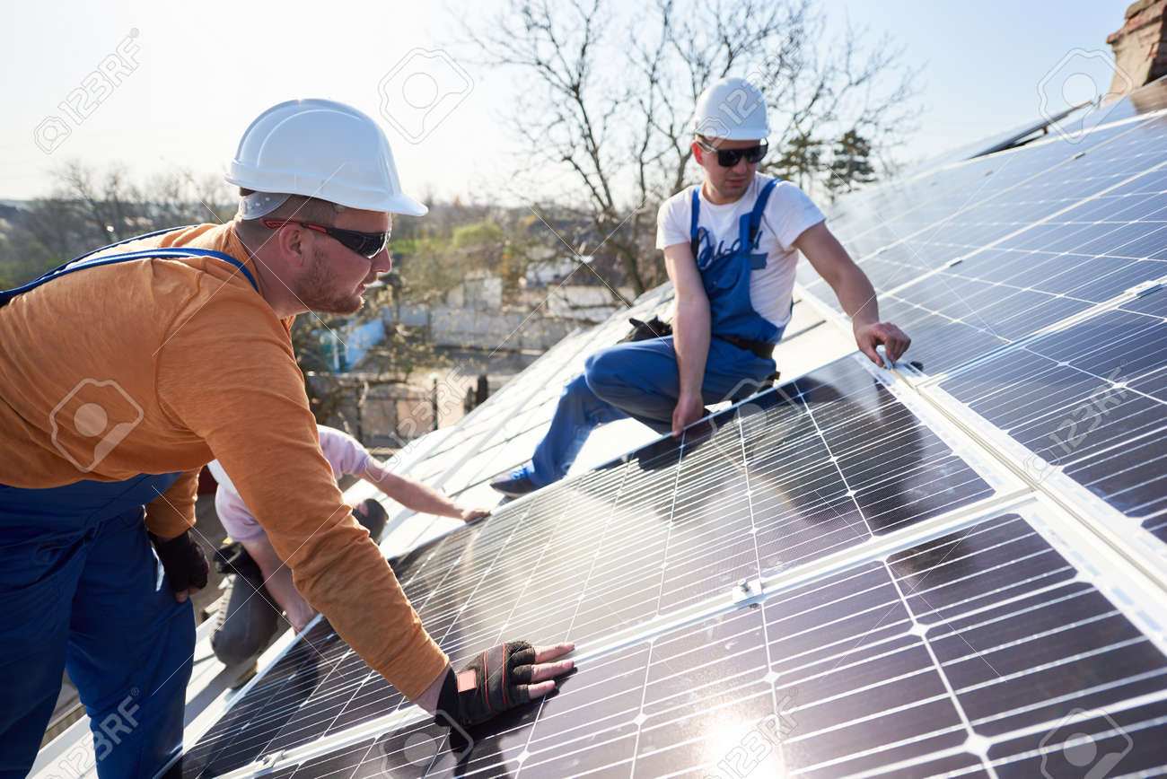 Male engineers installing solar photovoltaic panel system. Electricians mounting blue solar module on roof of modern house. Alternative energy ecological concept. - 155890874