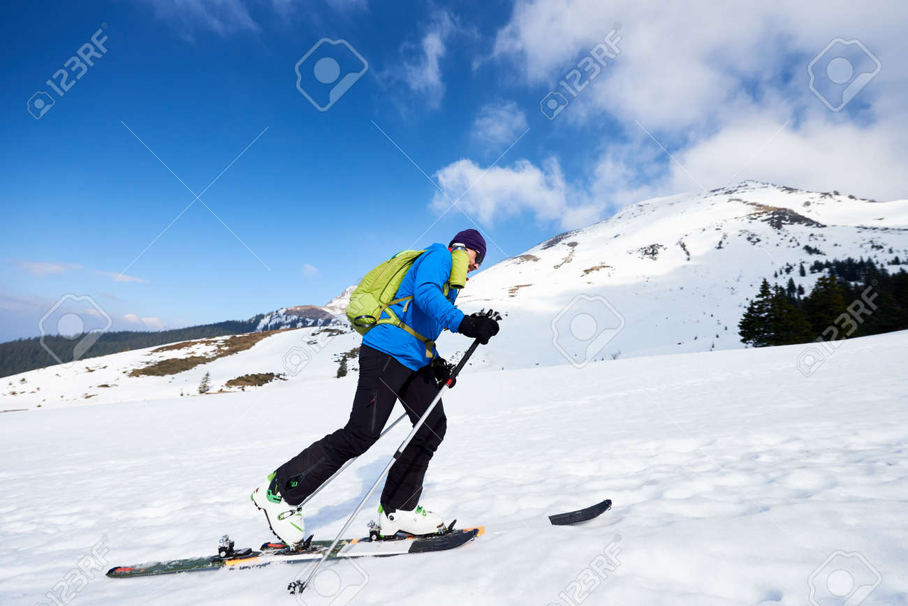 Happy tourist in colorful clothing and sunglasses with backpack climbing on skis in deep snow on background of bright blue sky and beautiful mountain. Winter vacations, active lifestyle concept. - 158193202