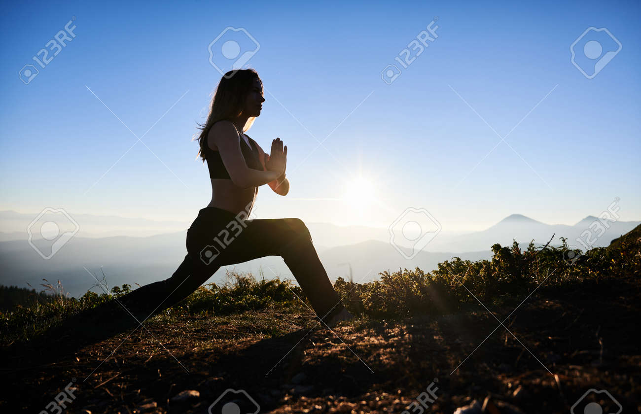 Side view of slim young woman in sportswear doing yoga exercise on grassy hill with blue morning sky on background. Female person doing morning gymnastics outdoors in mountains. - 173067771