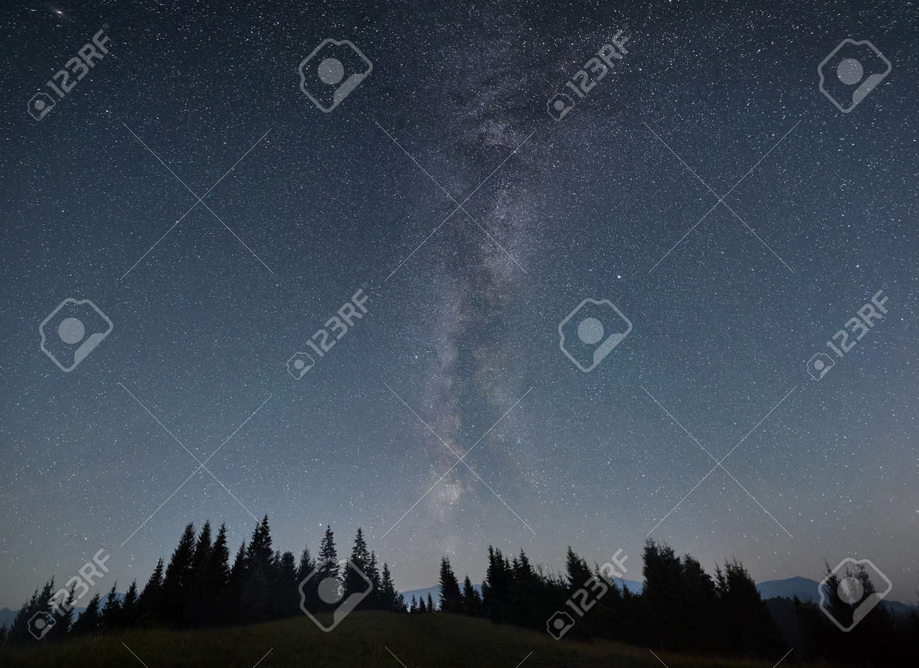 Night sky full of stars, Milky way in the mountains in summer. Galaxy above the hillside, beautiful night scene. Space background. Copy space. Astrophotography - 173107386