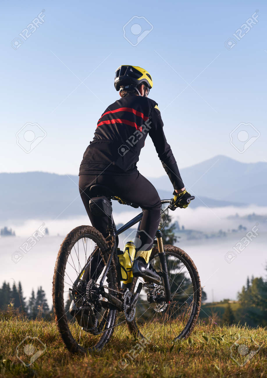Back view of young man in cycling suit riding bicycle on grassy hill. Male bicyclist enjoying the view of majestic mountains during bicycle ride. Concept of sport and bicycling. Vertical picture. - 173107322
