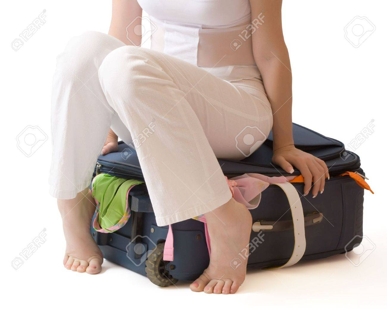 Barefooted woman sitting on a suitcase crammed full of clothes, isolated, with clipping path Stock Photo - 3217400