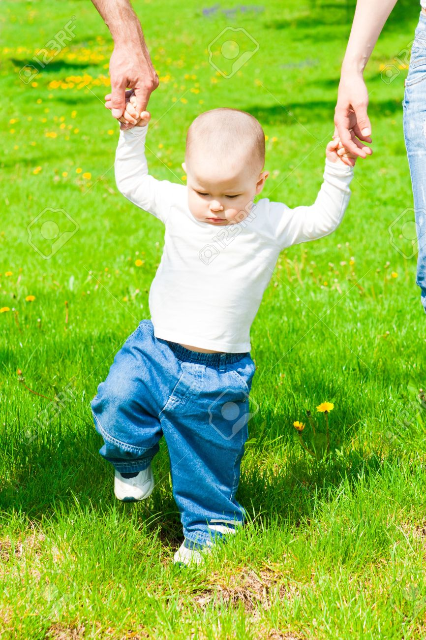 Baby walks in the park holding parents hands Stock Photo - 4861211