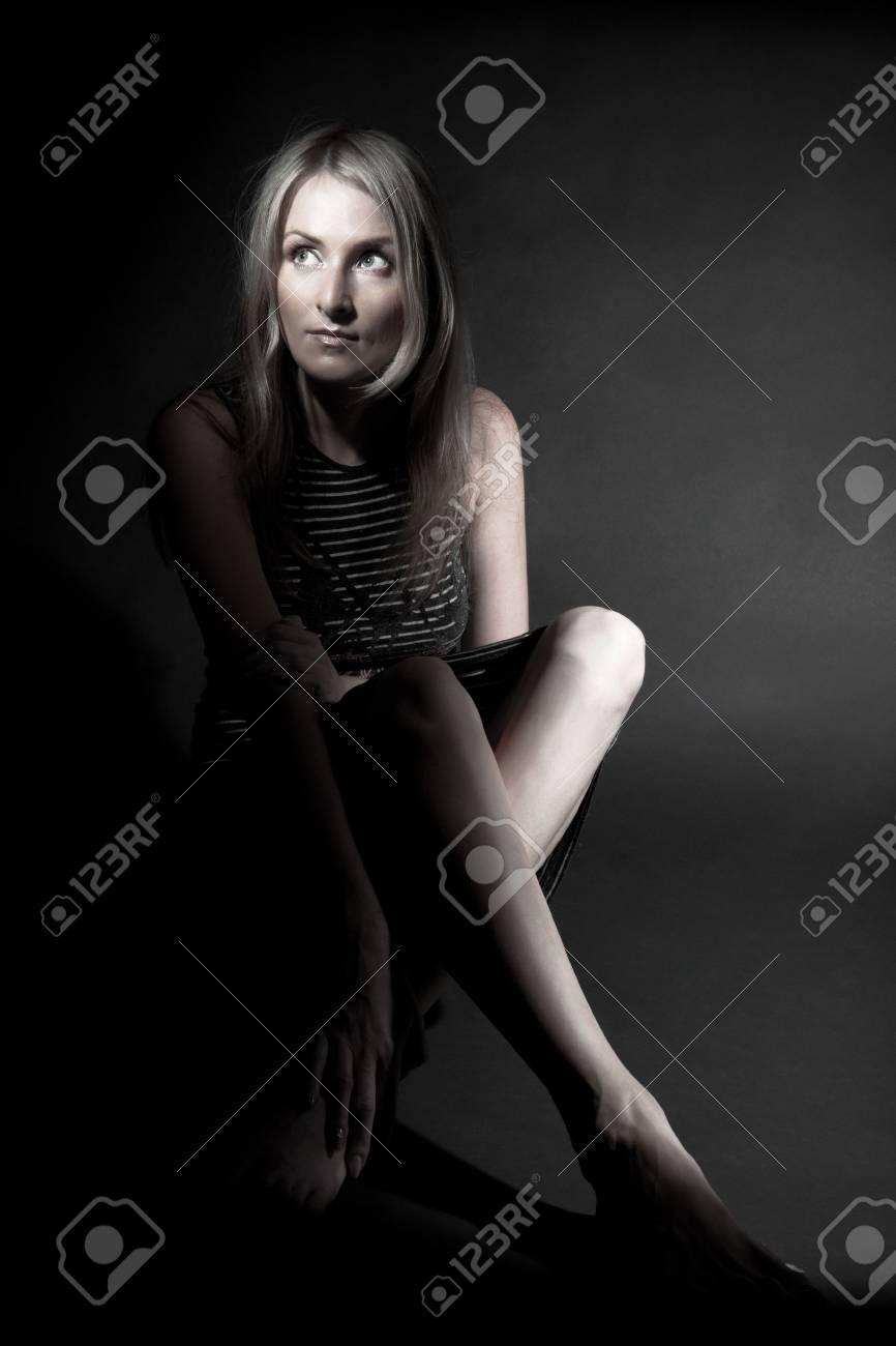 Girl sitting in spot of light over black Stock Photo - 5295562