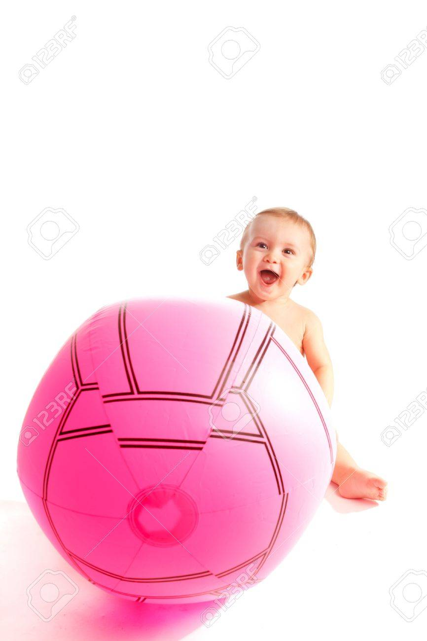Laughing baby sitting behind a large ball Stock Photo - 5781412