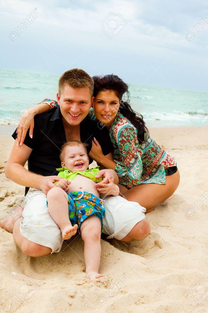 Happy kid and his parents at the coastline Stock Photo - 5832371
