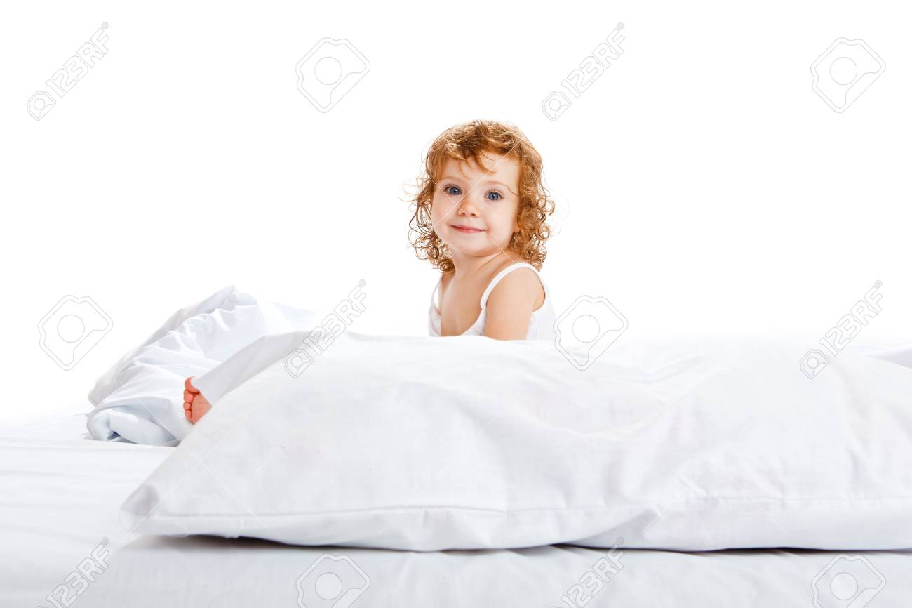 A cute girl in white sitting in bed Stock Photo - 5880387