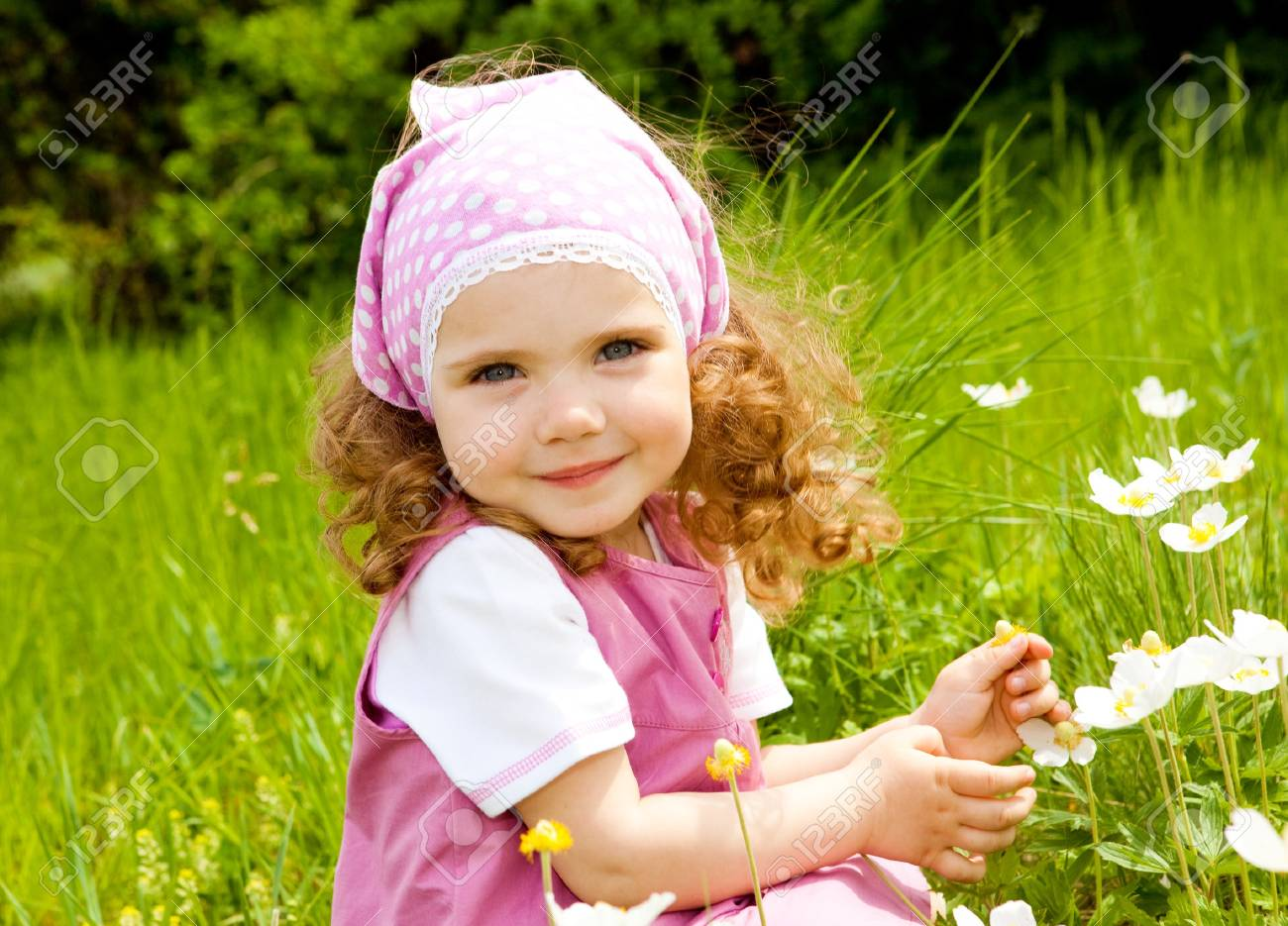 Smiling girl  on the meadow looking right at camera Stock Photo - 7001482