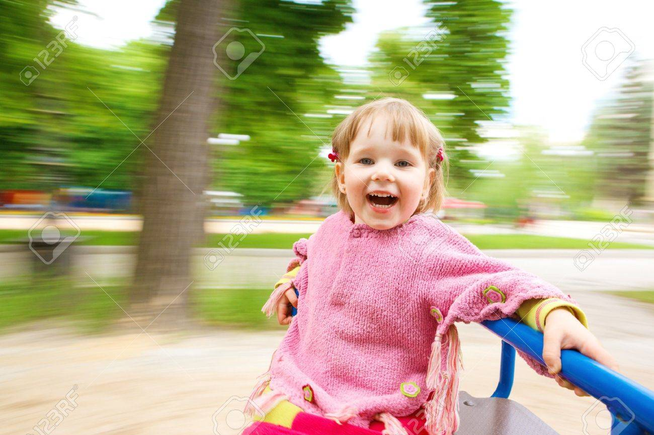 Happy girl having fun on the roundabout Stock Photo - 7072614