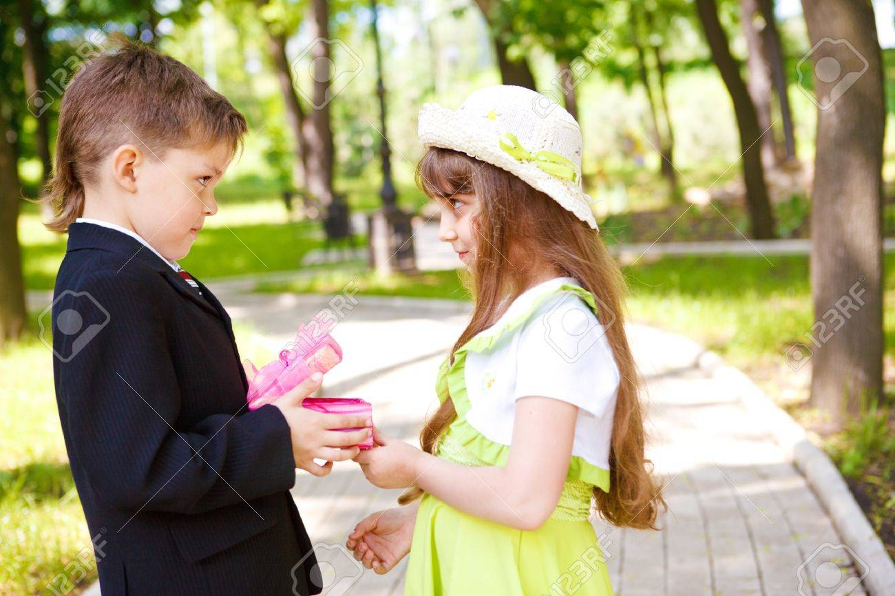 Preschool boy in suit giving a present box to the sweet girl Stock Photo - 7221268
