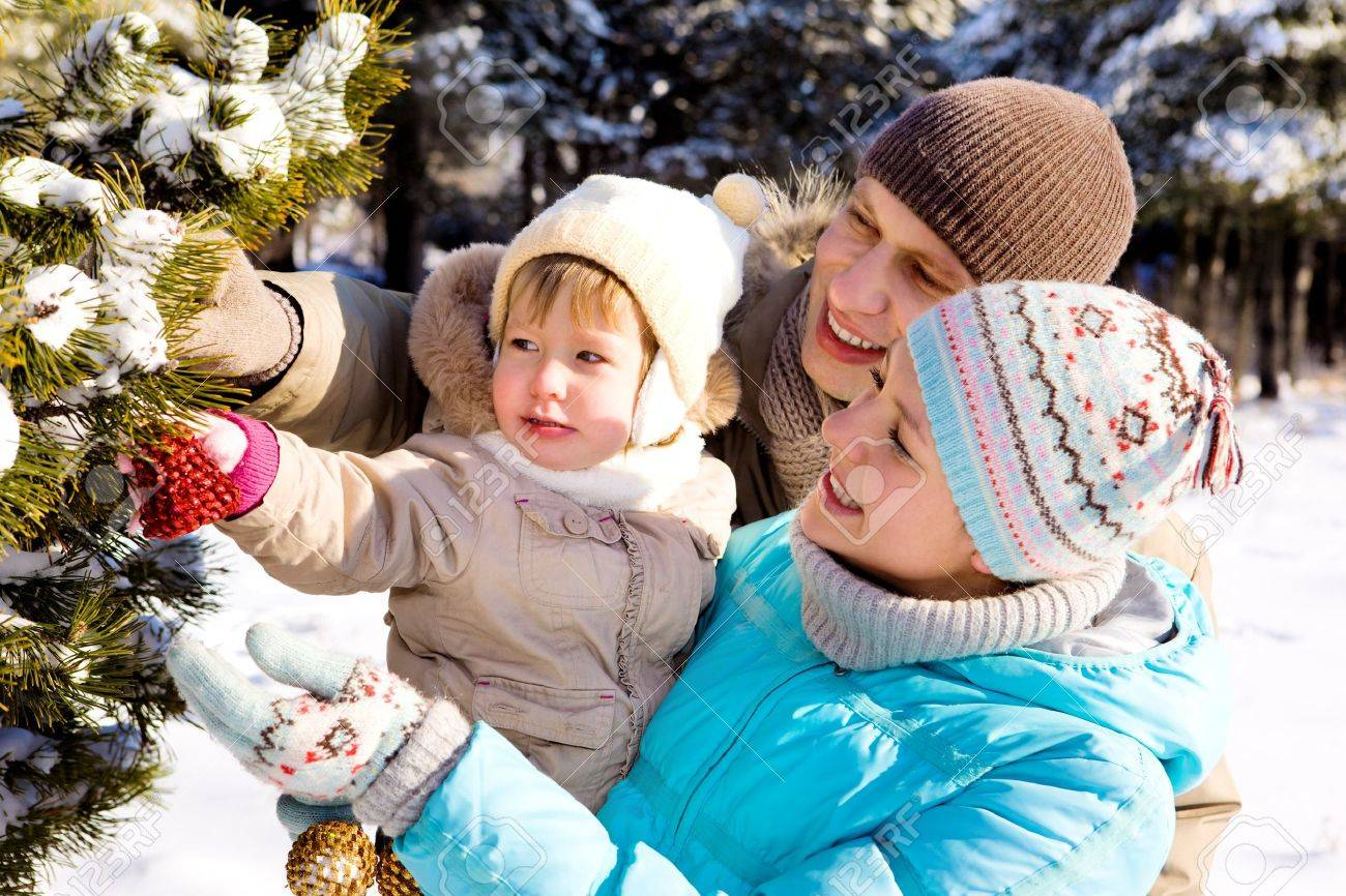 Parents and daughter decorating Christmas tree in a winter park Stock Photo - 7367492