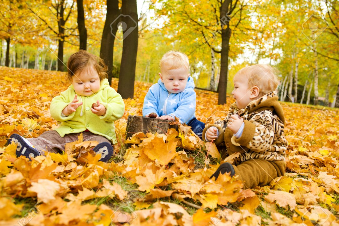 Babies playing with chestnuts in the autumn park Stock Photo - 7498421