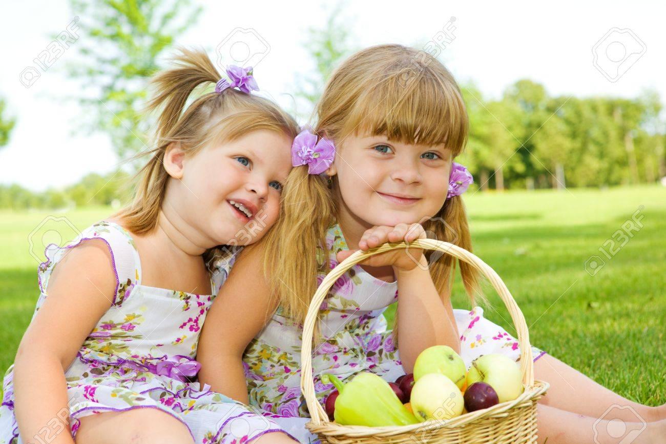 Two sweet kids in garden with fruit basket beside Stock Photo - 7498602
