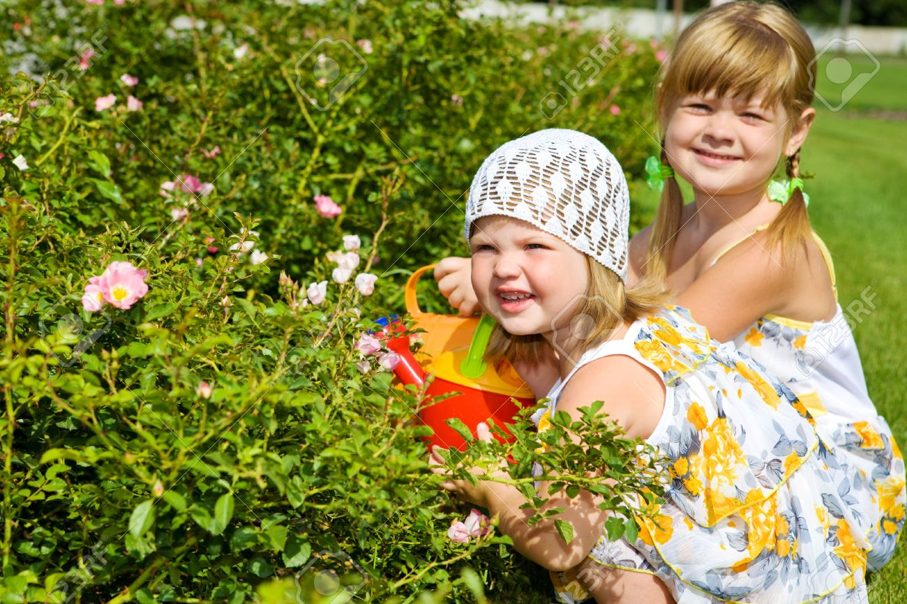 Two sweet kids watering flowers in the garden Stock Photo - 7498409