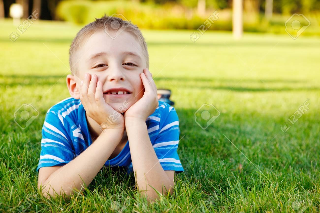 Boy lying on grass laughing Stock Photo - 7613342