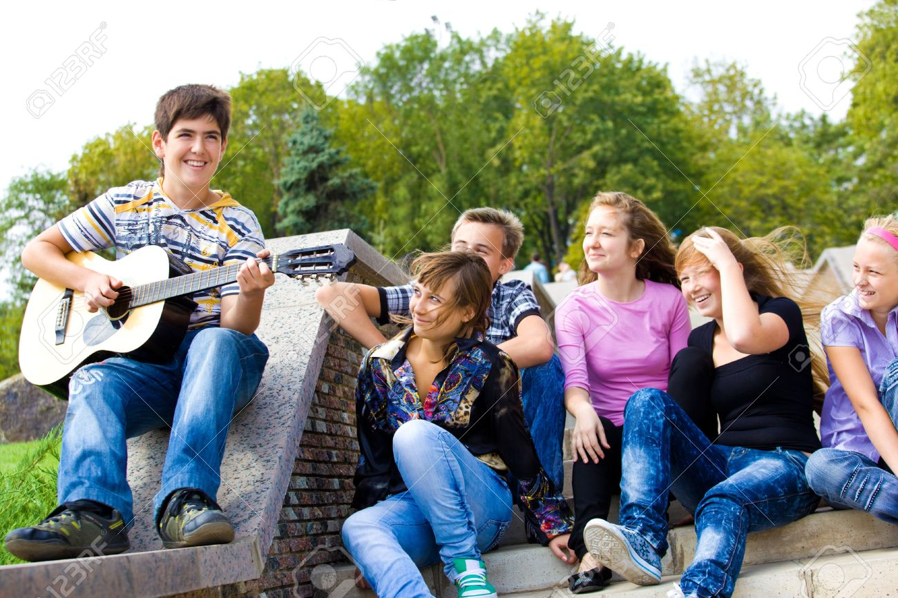 Cute teenage guy playing guitar for his friends Stock Photo - 7872225