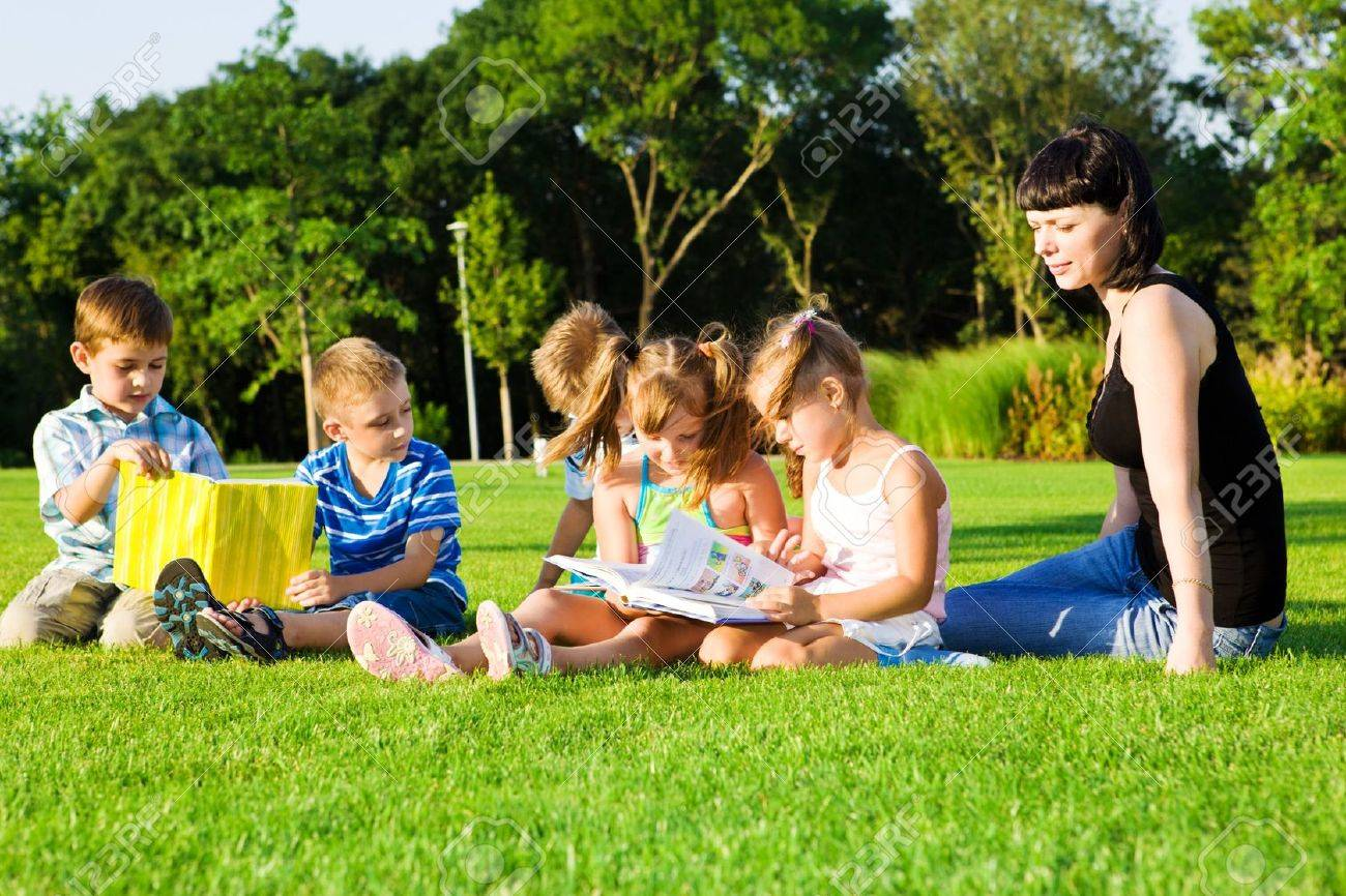 Lovely preschoolers with books, teacher beside them Stock Photo - 7918682
