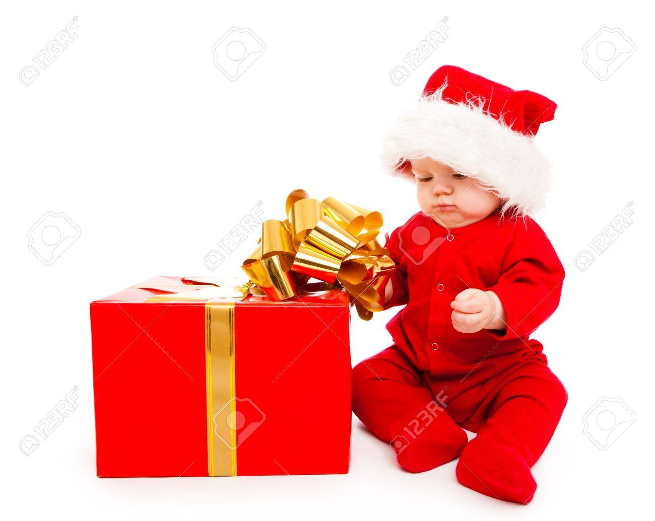 Baby in red clothing and Santa hat busy packing Christmas present Stock Photo - 8168508