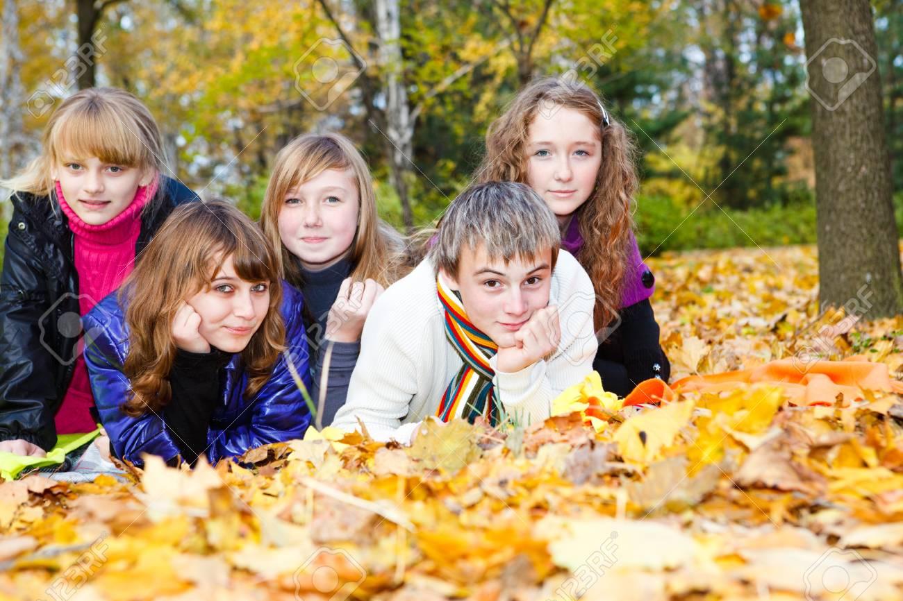 Group of joyful teens lying on autumnal leaves Stock Photo - 8168573