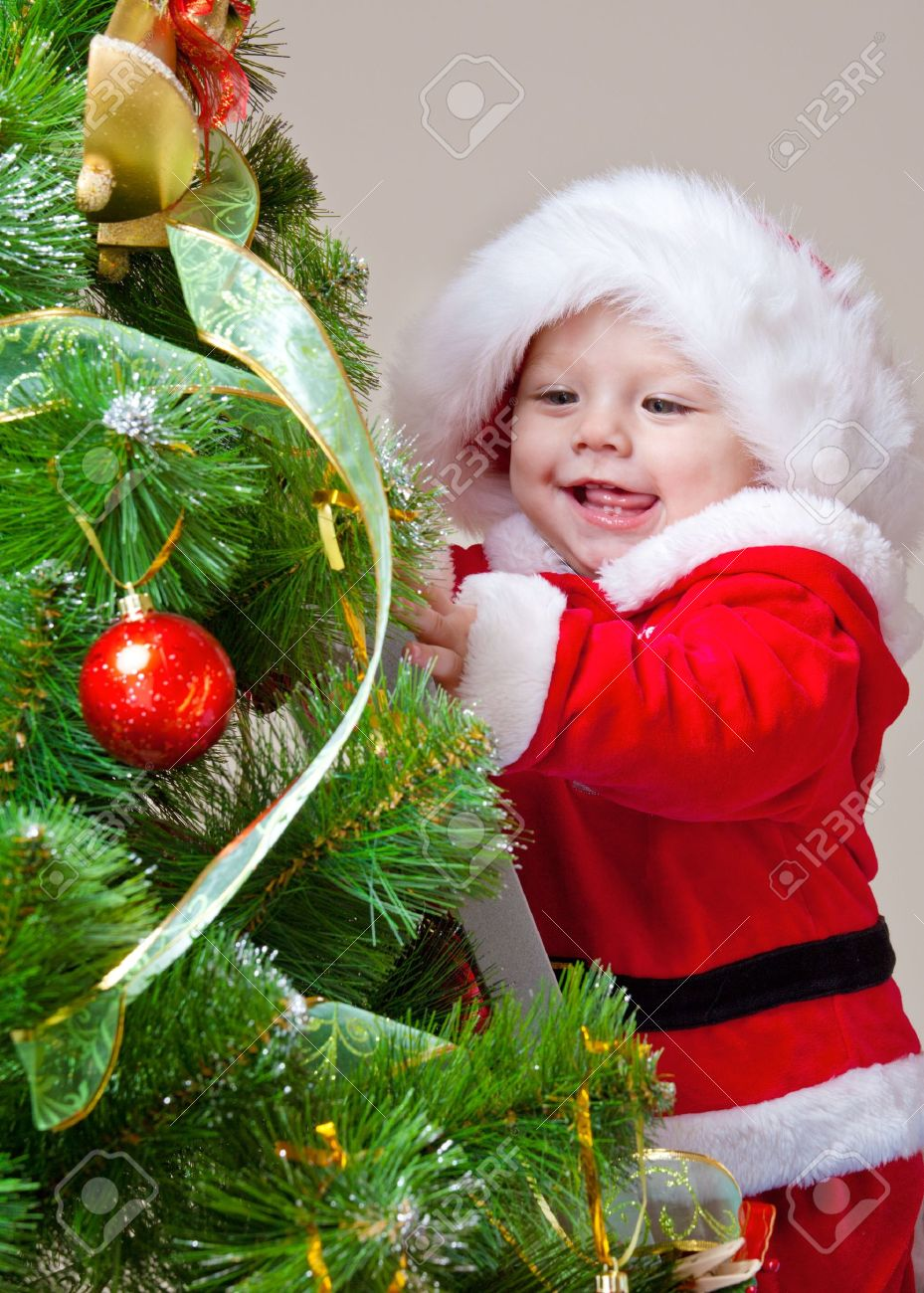 Baby decorating Christmas tree, over gray - 8168634