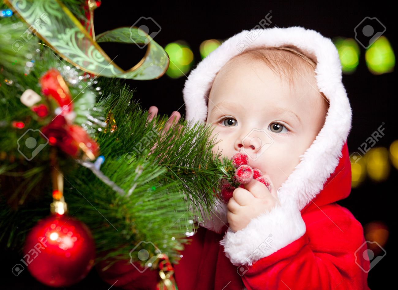 Portrait Of Santa Baby Beside Christmas Tree Stock Photo, Picture ...