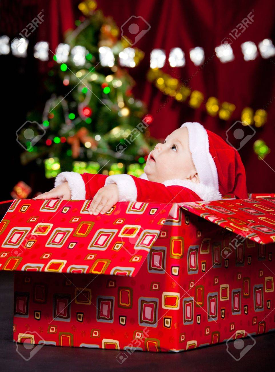 Baby in Christmas costume sitting in a large present box and looking up Stock Photo - 8372922