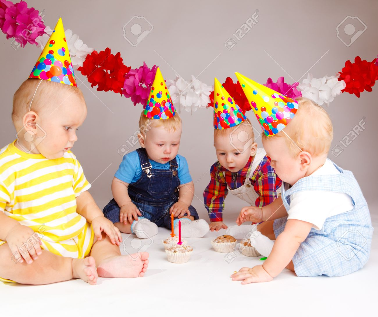 Group Of Babies Looking At Cupcakes With Birthday Candles Stock Photo