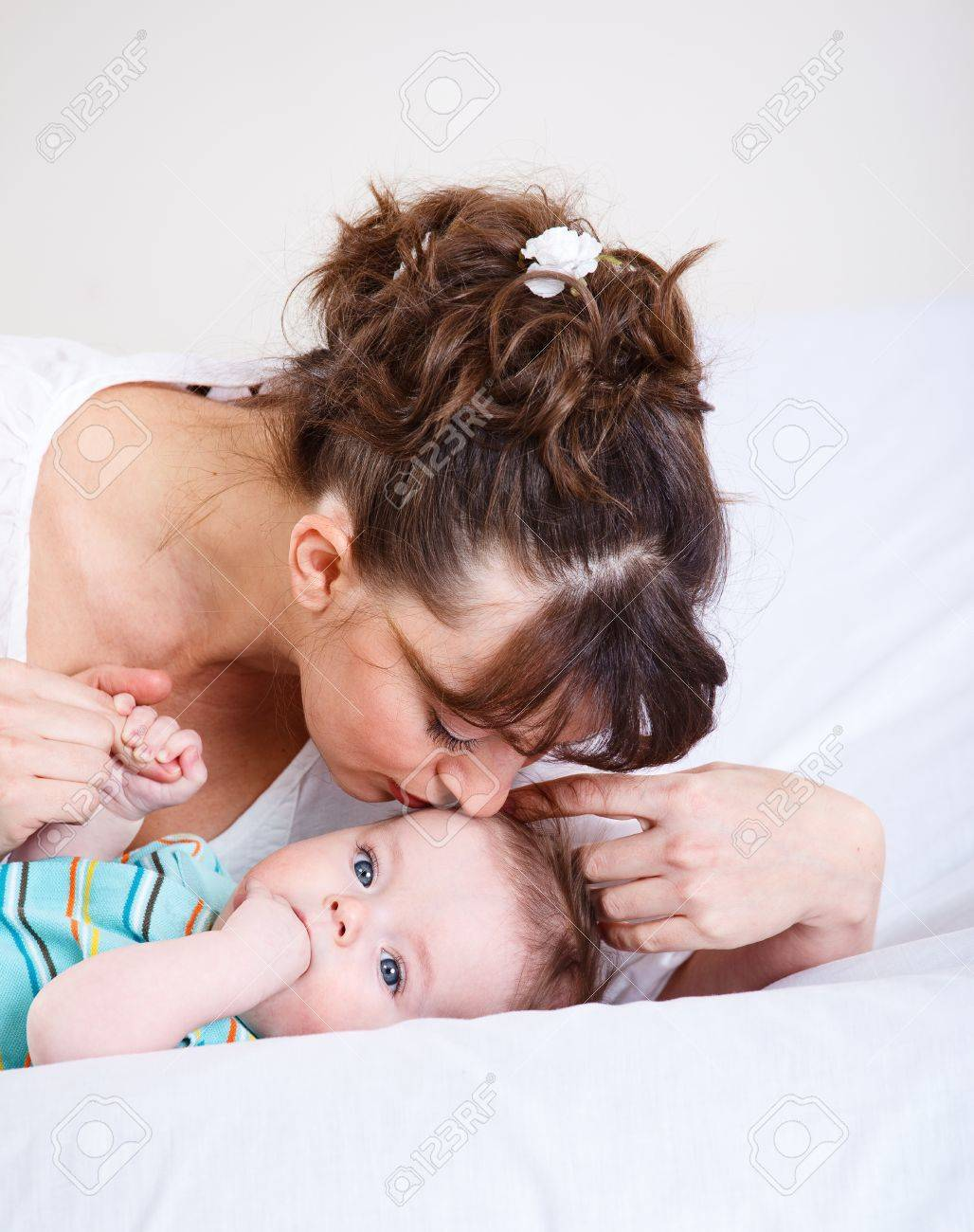 Woman kisses baby lying in bed Stock Photo - 9060838