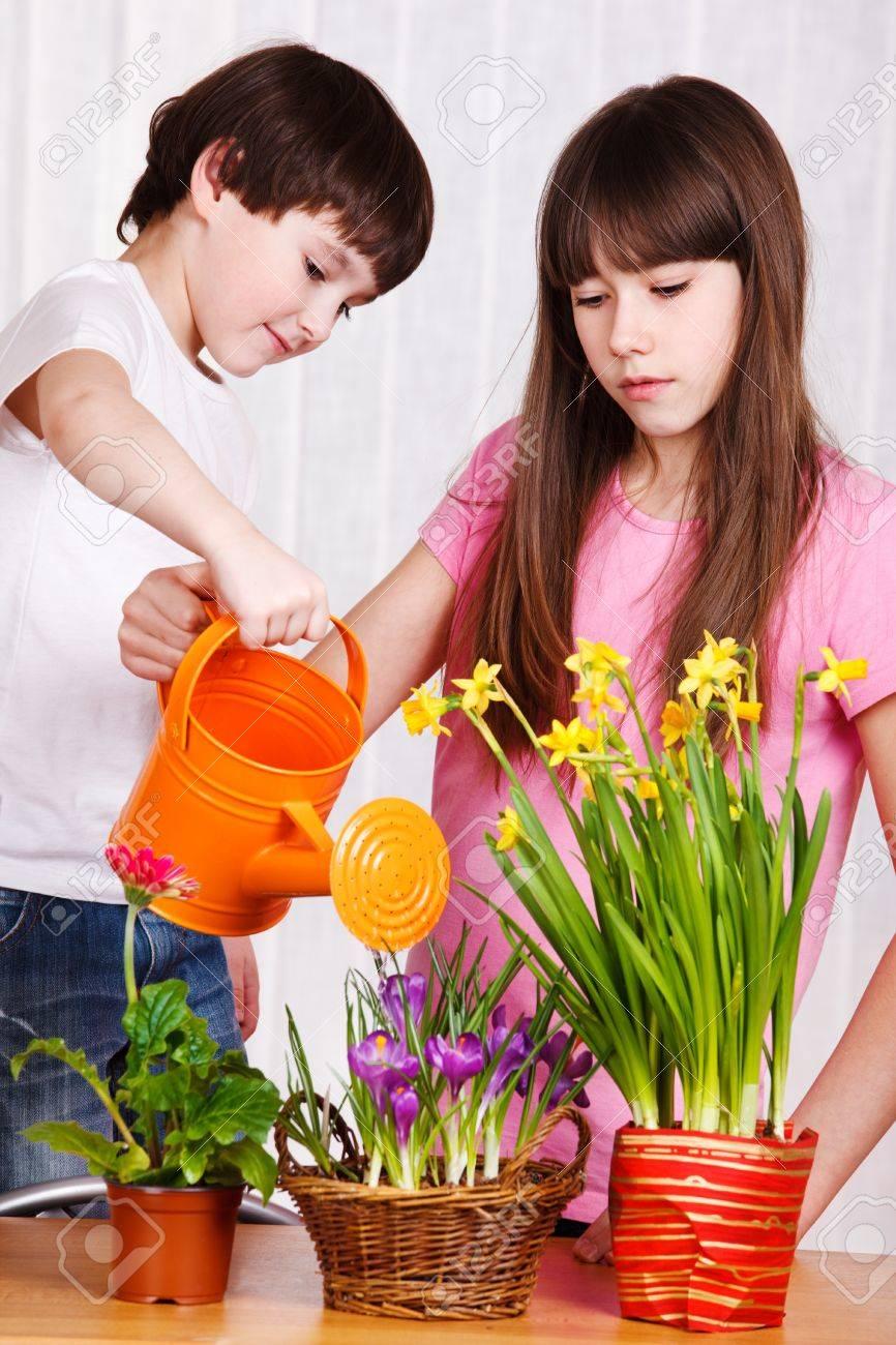 Two cute kids watering flowers Stock Photo - 9060856