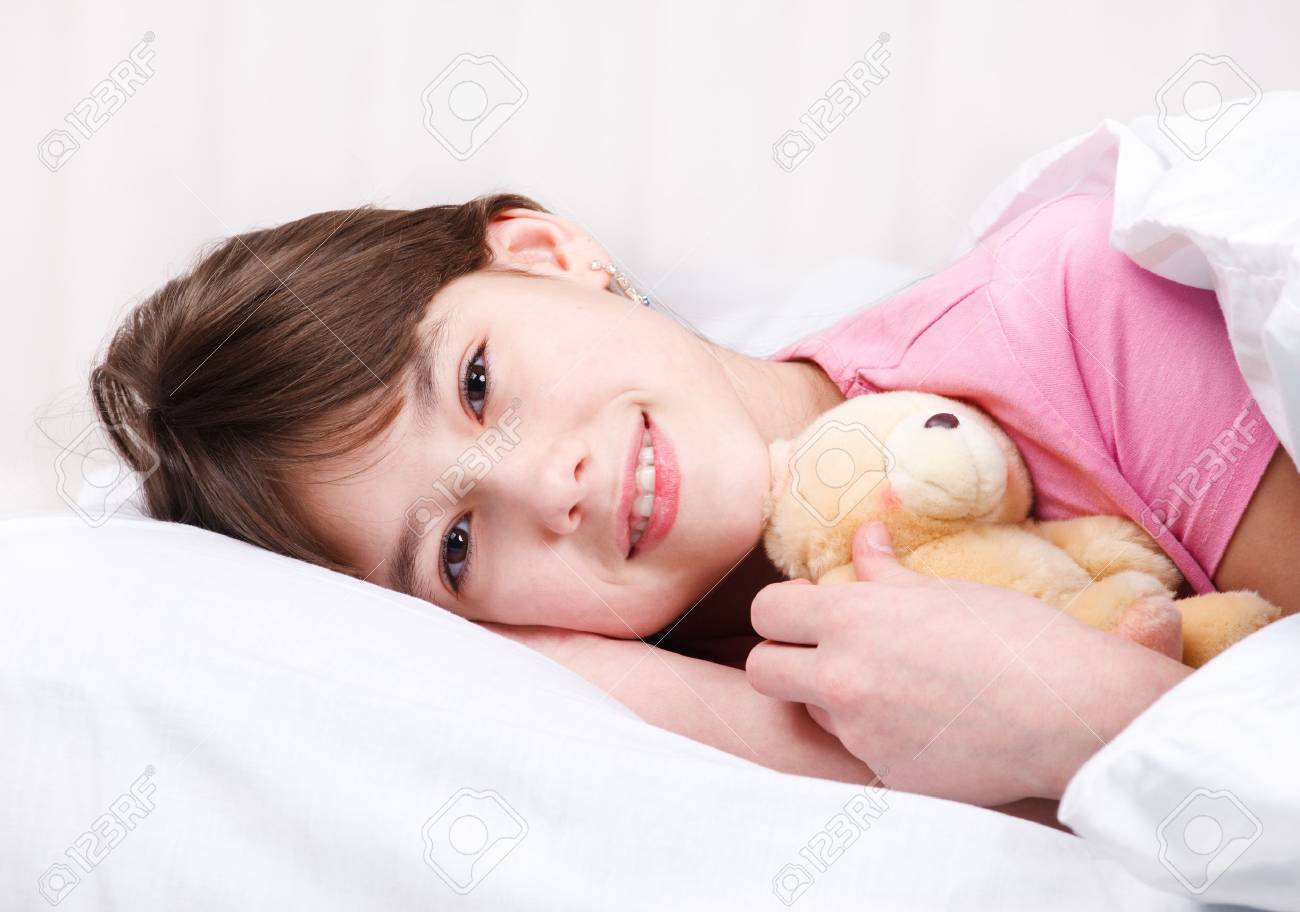 Teenage girl with a bear toy lying under blanket Stock Photo - 9060854