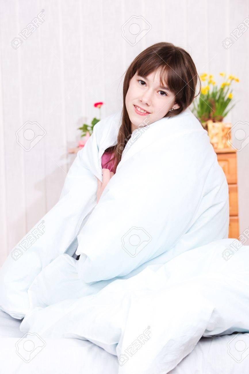 Teenage girl wrapping her body into blanket Stock Photo - 9060841