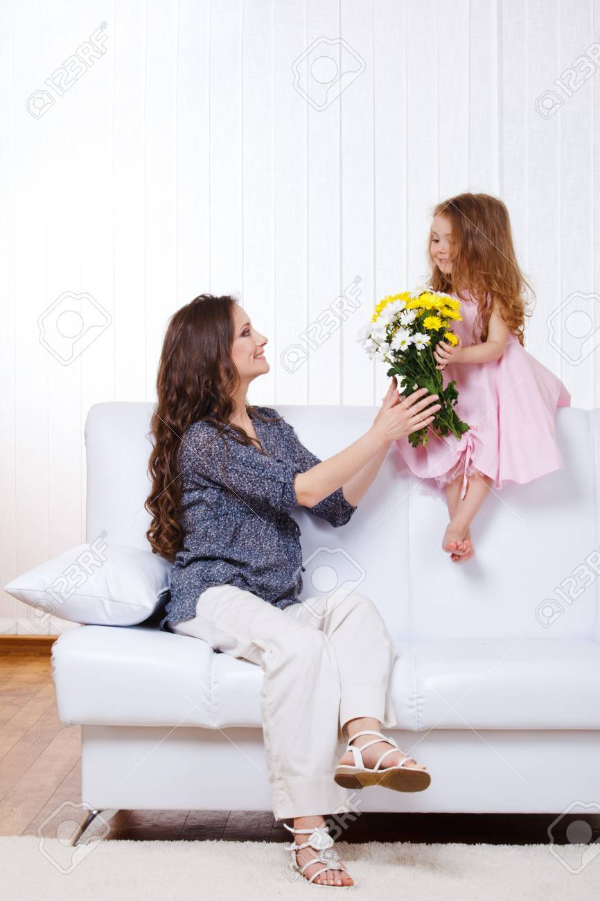 Girl presenting mother yellow and white flowers Stock Photo - 9330586