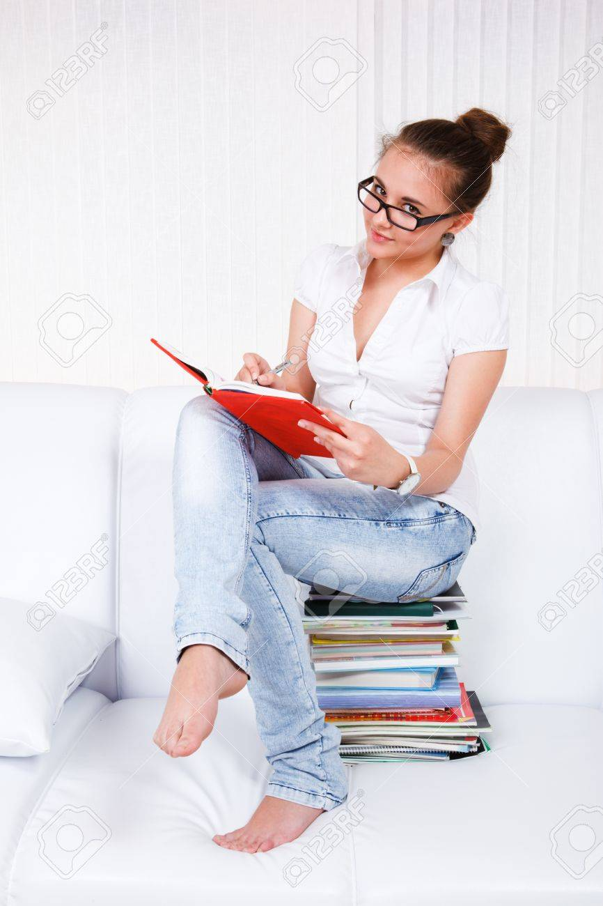 Student sitting in a living room and reading Stock Photo - 9354788