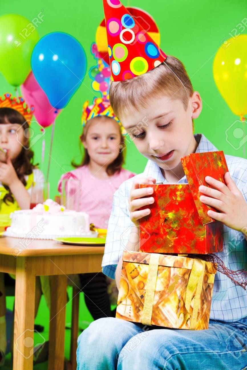 Preschool boy in party hat looking into present box Stock Photo - 9589200