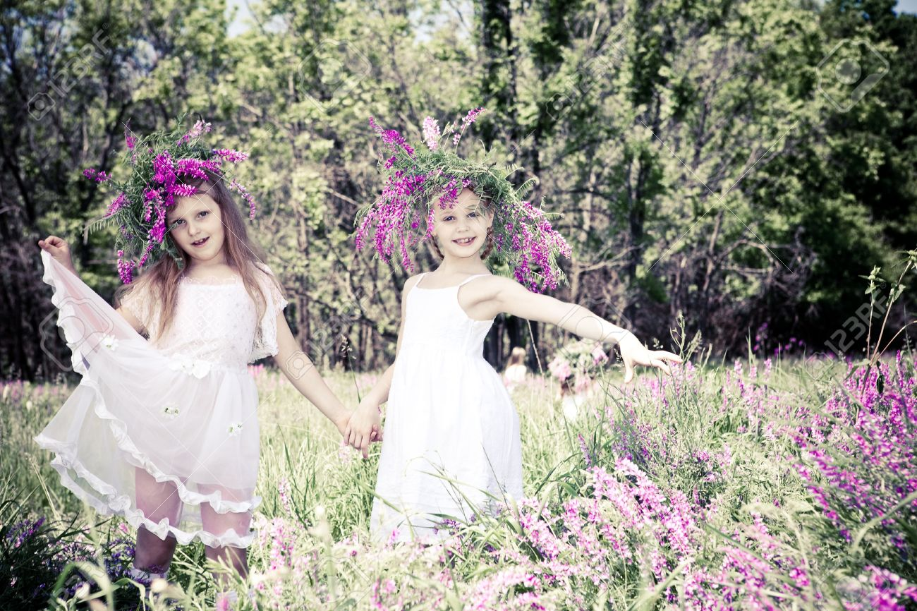 Two lovely girls with headwreaths, holding hands Stock Photo - 9797647