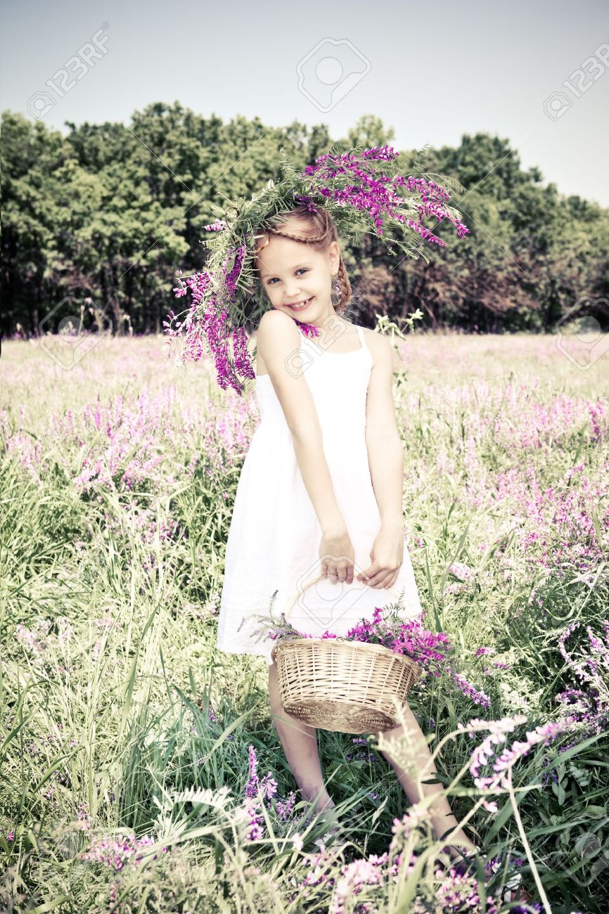 Beautiful blond girl holding basket with flowers Stock Photo - 9797677