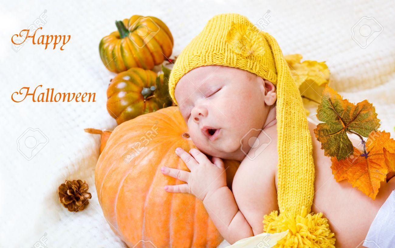 Happy halloween greeting card with baby sleeping on a pumpkin Stock Photo - 10364800