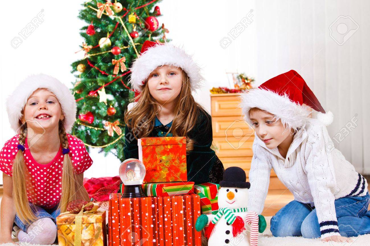 Three Lovely School Aged Kids Sit Beside Christmas Presents Stock ...