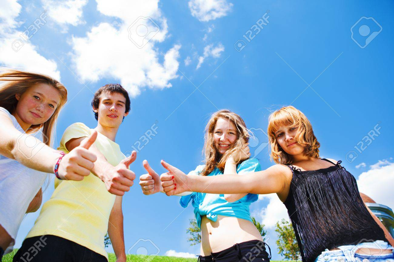 Smiling teens showing thumbs up - 10661658