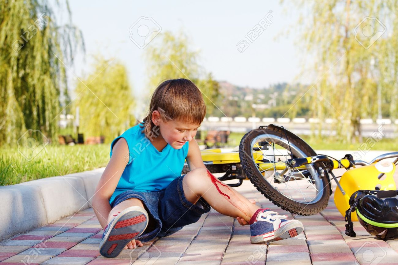 Crying boy with a bleeding injury sitting beside the bike that he has fallen from - 10661665