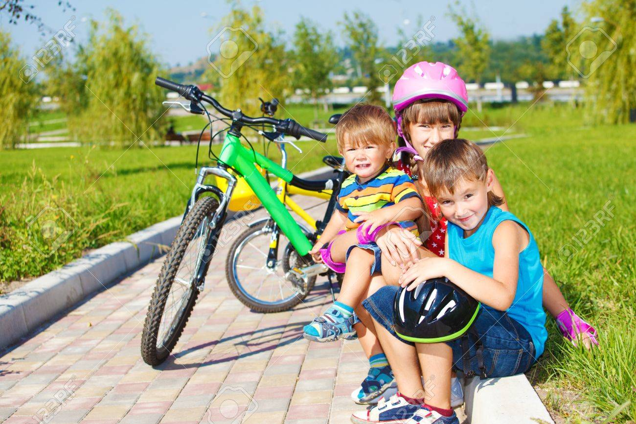 Siblings sitting on grass, their bikes stand behind Stock Photo - 10661675