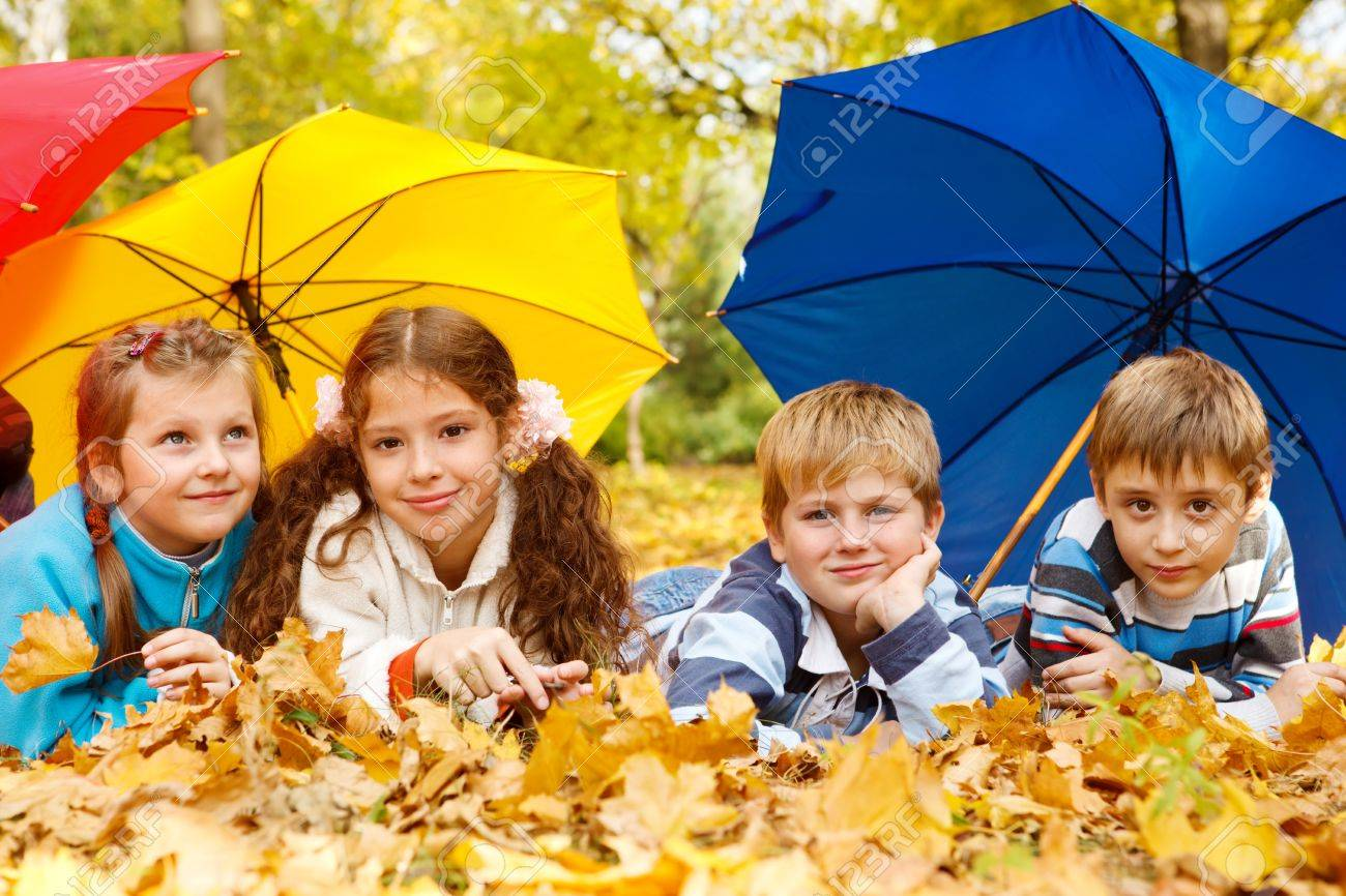 kids group hiding under colorful umbrellas stock photo picture