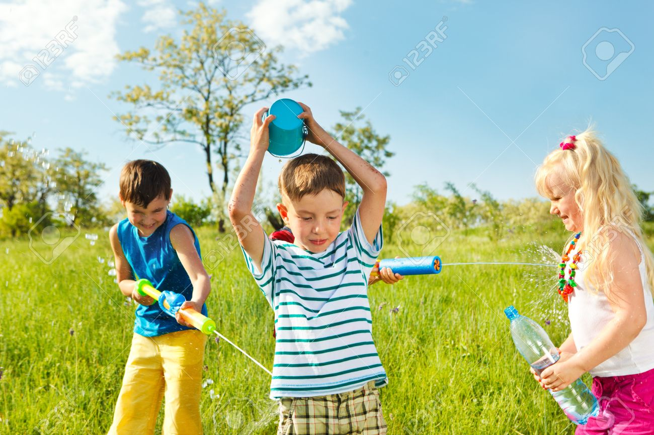 kids play water Soaked happy kids playing with water in the meadow Stock Photo - 13885228