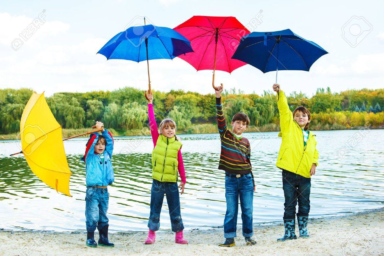 kids in autumn clothing holding colorful umbrellas stock photo