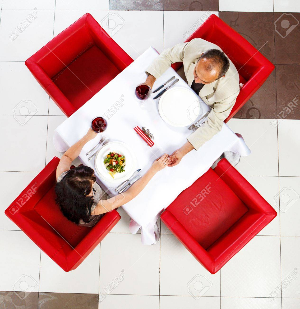 Top view on middle aged man and woman holding hands in a restaurant Stock Photo - 18293472