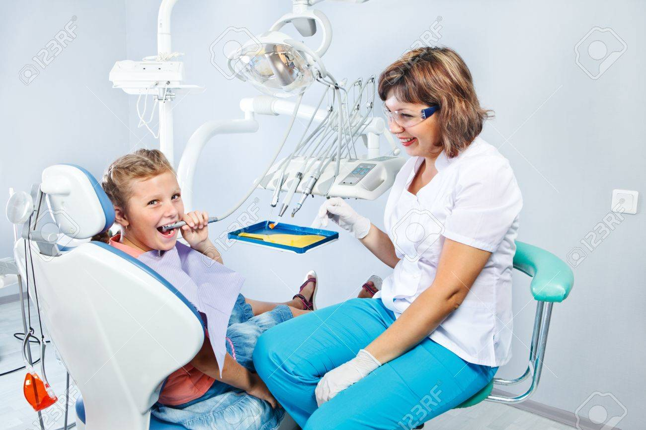 Kid playing with dental drill during  her first pediatric dentist visit Stock Photo - 18562504