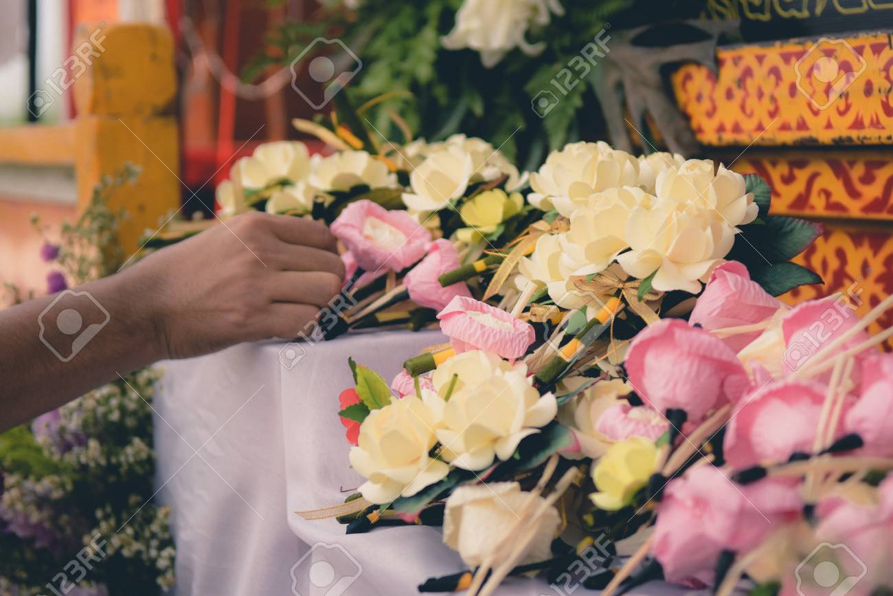 Woman Putting Funeral Flower On Coffin At Funeral Stock Photo