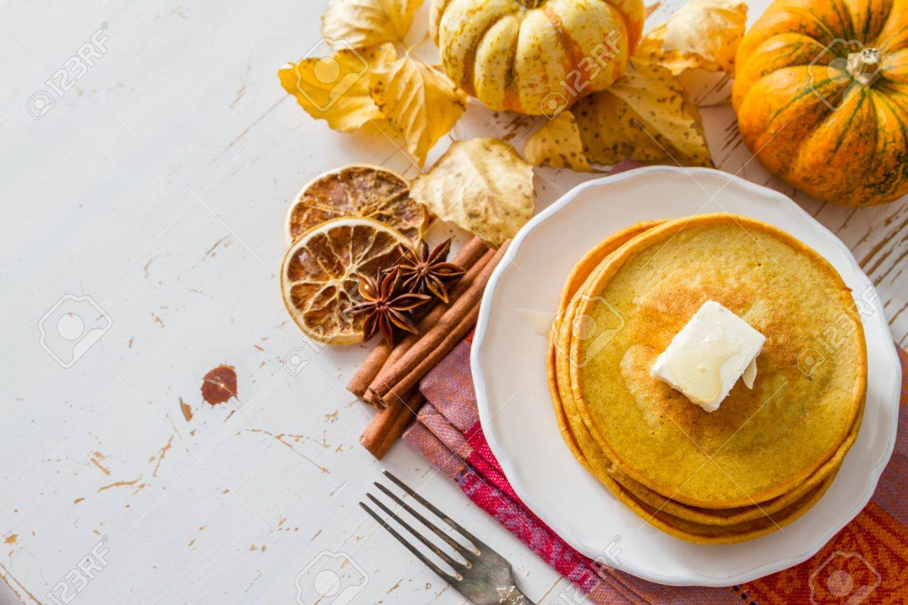 Pumpkin pancakes on white plate with butter and honey, white wood background Stock Photo - 48432722