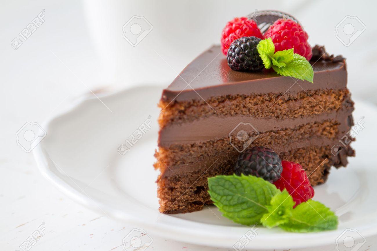 Chocolate cake slice on white plate mint berries, white background Stock Photo - 48434200