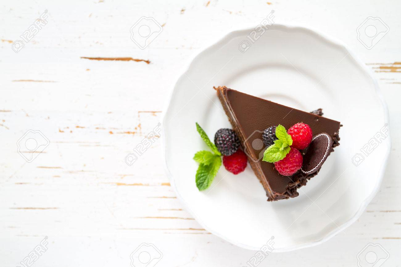 Chocolate cake slice on white plate mint berries, white background Stock Photo - 48434201